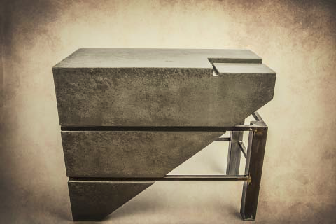 An abstract end table with metal and concrete.