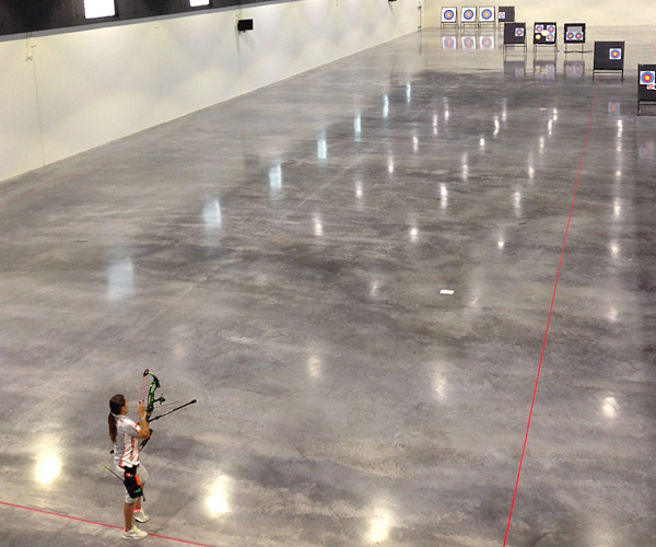 Polished Concrete Archery Range used polished concrete as it's surface of choice in the U.S. Olympic Training Center. Girl shooting arrow over polished concrete prior to the U.S. Olympic games.