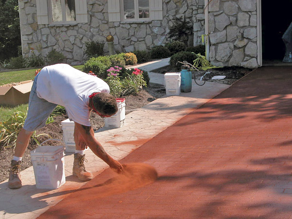 applying dry shake color over a concrete stencil