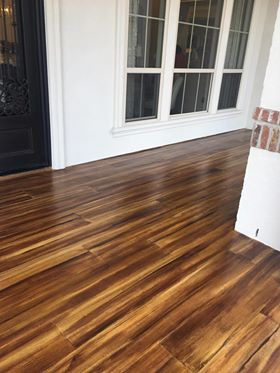 Wood look concrete in a living room space with brown concrete stains.