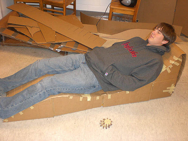 design a concrete lounge chair - A student tests a cardboard mockup.