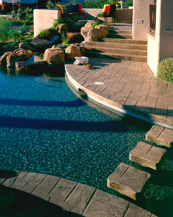 stamped concrete deck with gorgeous pool and rock features