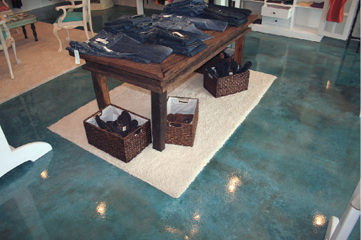 Clothing table in a retail store on top of a blue stained concrete floor.