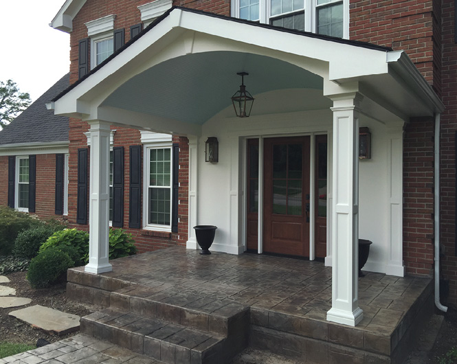 grey front deck with stamped concrete entryway