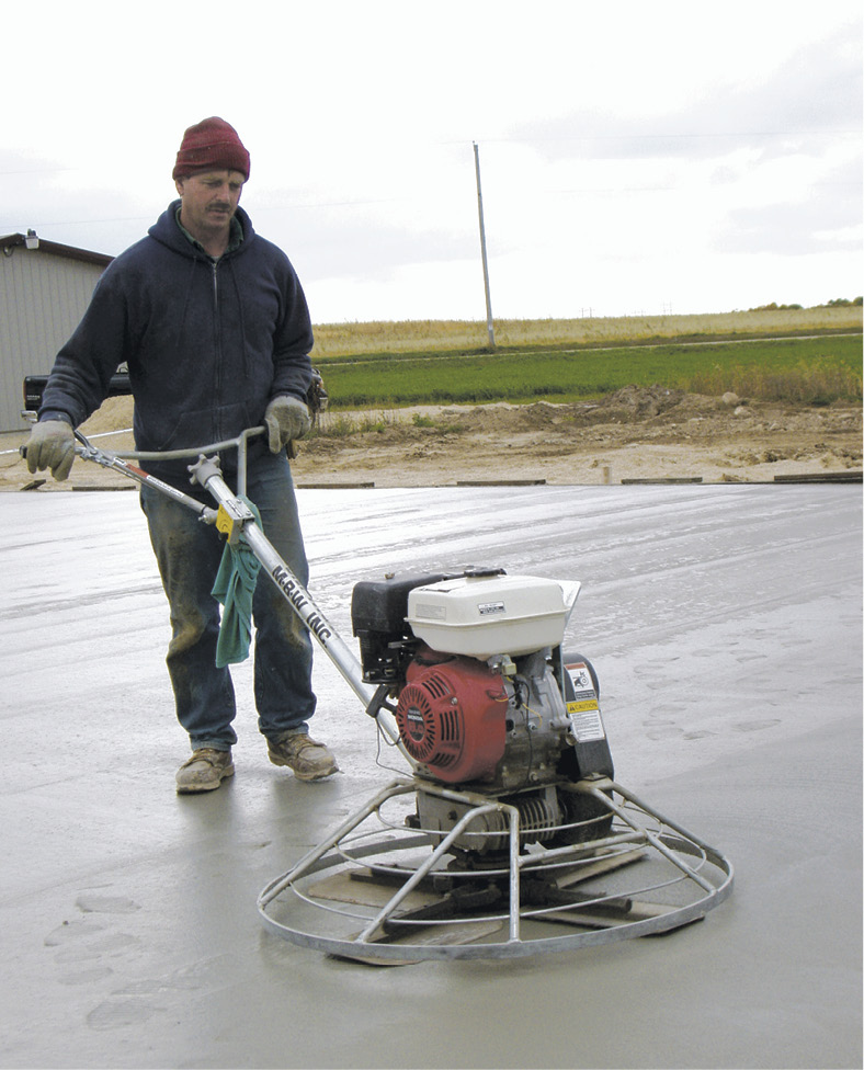 a crew member using a power trowel on concrete