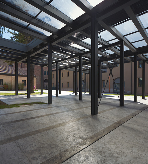 Concrete floor is dignified by the clear roofing with steel support beams.