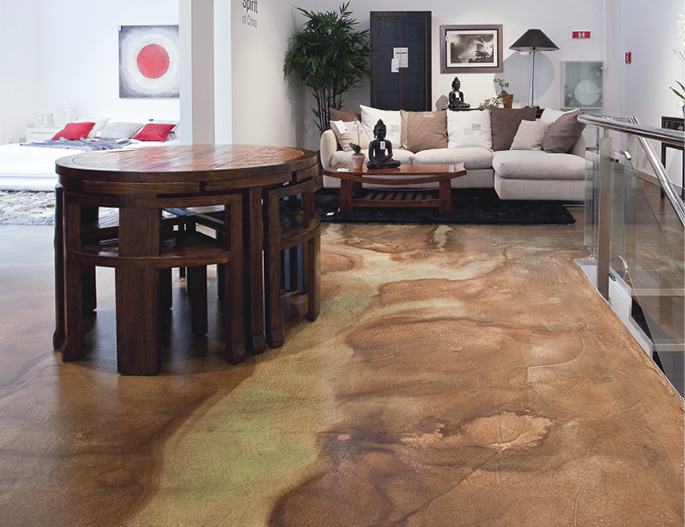 Two tone stained concrete living room floor with oblong table & small chairs.