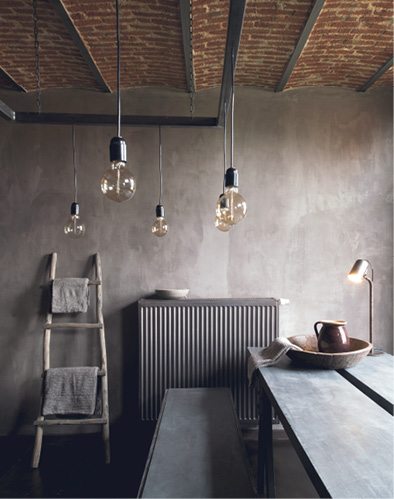 Gray concrete table with retro lights hanging from ceiling.