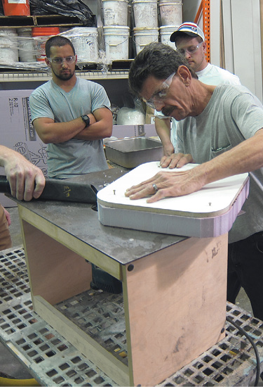 Here, class participants shape a foam sink knockout on a router table to fit a wooden sink-hole template.