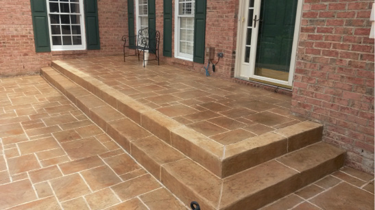 Stamped concrete in a tile and grout look back porch of a brick home with green shutters and white trim.