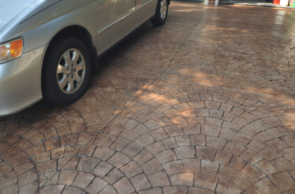 A fan patterned concrete stamp has been used on this heavily used driveway that has been stained and sealed.