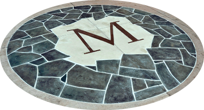 A concrete stencil has been custom made by Salzano Custom Concrete with a M representing a clients last name.