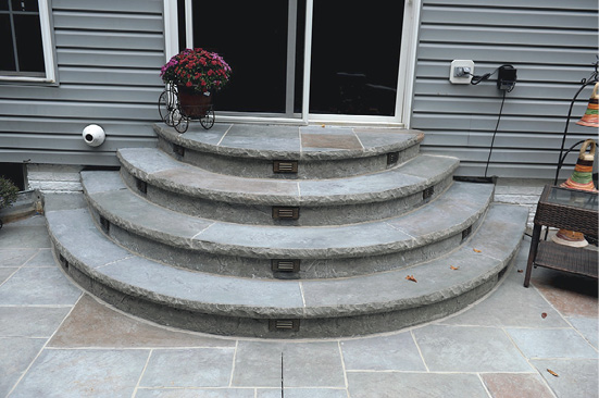 Formed concrete with a edge form on theses rounded steps lead to a back sliding glass door.