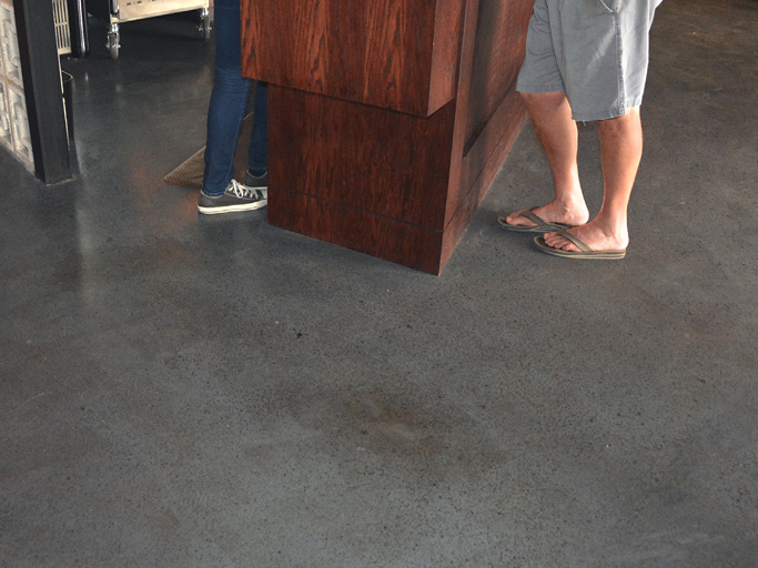 The first Gino's Pizza to open in Phoenix features a floor colored with iCoat's One Day Stain in medium gray with a brown accent. The area seen here at the hostess stand near the restaurant entrance is where a red-colored slab placed in 1957 meets up with a new pour.