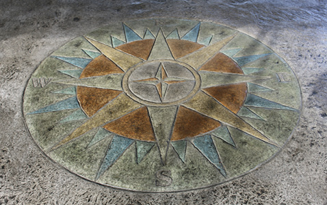 The stamped concrete compass displays the colorful hues in more muted tones of concrete stains.