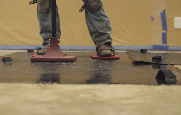 A tamper and texture skin shoes on a stamping mat at a concrete overlay training class.