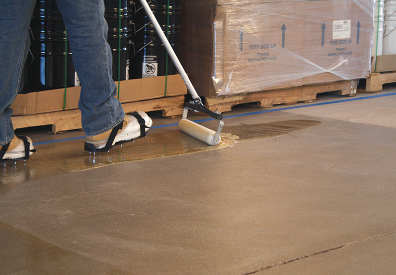 using an epoxy coating for remediating moisture in concrete can be a perfect solution as seen here with a contractor using a roller to apply the coating