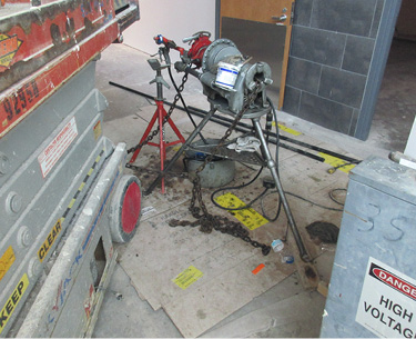 Machine leaking oil onto a protective barrier for the concrete surface below.