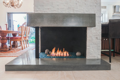 Interior corner modern fireplace with upper concrete hearth and stoop.