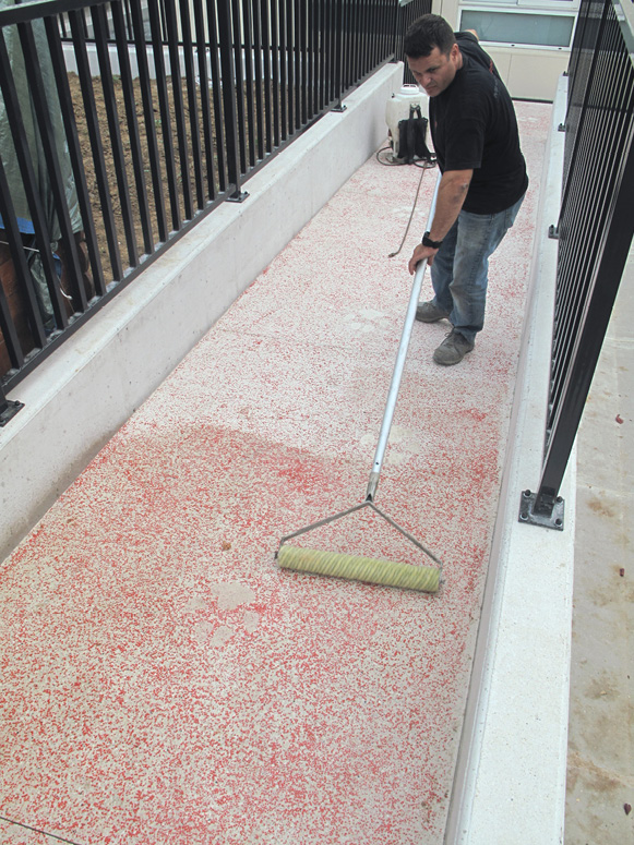 Rolling on a surface retarder onto a freshly placed concrete overlay.