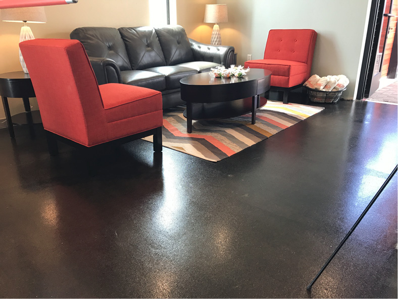 Instead of staining the concrete separately and then applying the epoxy in the walkways, kitchen, restrooms and laundry facilities, the Quest crew mixed a black Ameripolish stain with Kretus Top Shelf Epoxy and applied both products in one step,