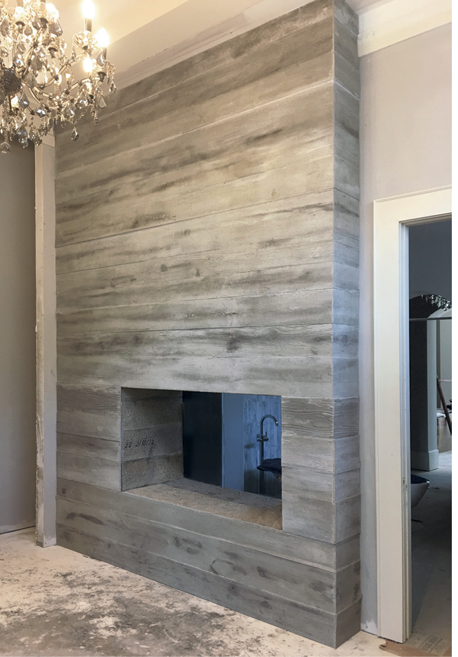 A concrete fireplace face in a silvery gray wood grain finish that stands 14 feet high and 10 feet wide. Photos courtesy of Concrete In-Counters