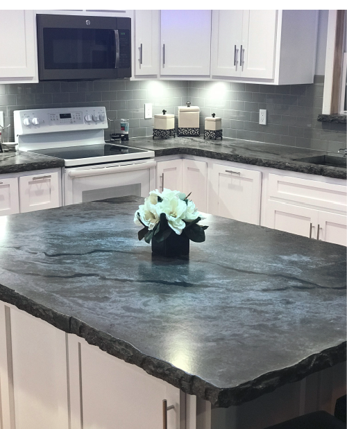 Dark black gray marbled concrete countertop with a broken rock edge. Kitchen island with white cabinets. Photos courtesy of Concrete In-Counters