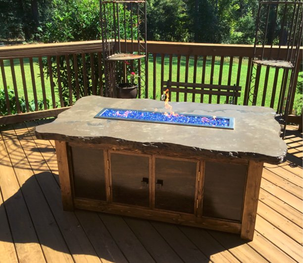 Outdoor fire table made with a concrete countertop. Features a row of blue glass aggregate with flame tube. Photos courtesy of Concrete In-Counters concrete countertop firepit