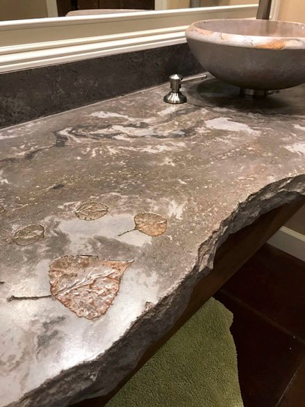 Concrete Countertop in a bathroom with leaf impressions and a broken edging. Concrete vessel sink. Photos courtesy of Concrete In-Counters