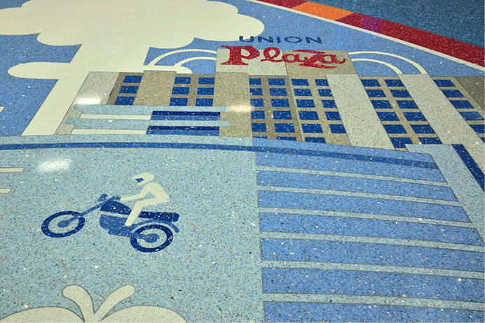 Using these water jet-cut terrazzo pieces allowed the artist to create an extremely detailed design, without using many divider strips, where small details were included, such as the airplane's windows, hotel names or the welcome sign
