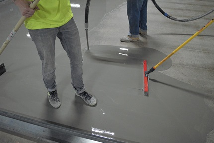 Contractor's placing a microtopping on a floor with spreaders.