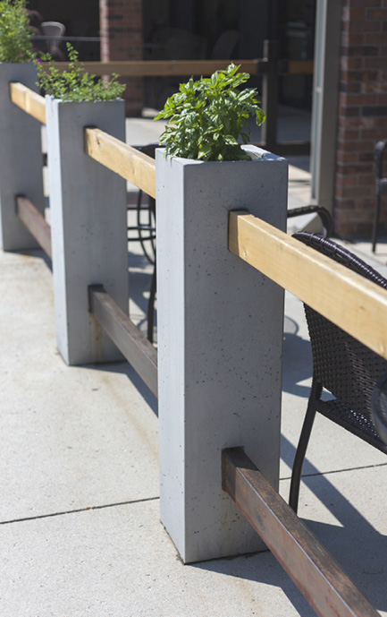 Precast concrete fence poles on a city side walk to surround a restaurant eating area.