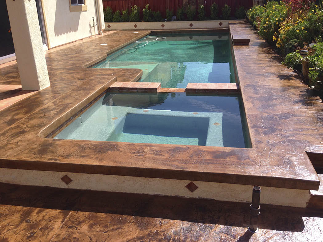 Rectangular swimming pool sits next to a square hot tub surrounded by stamped and textured concrete.