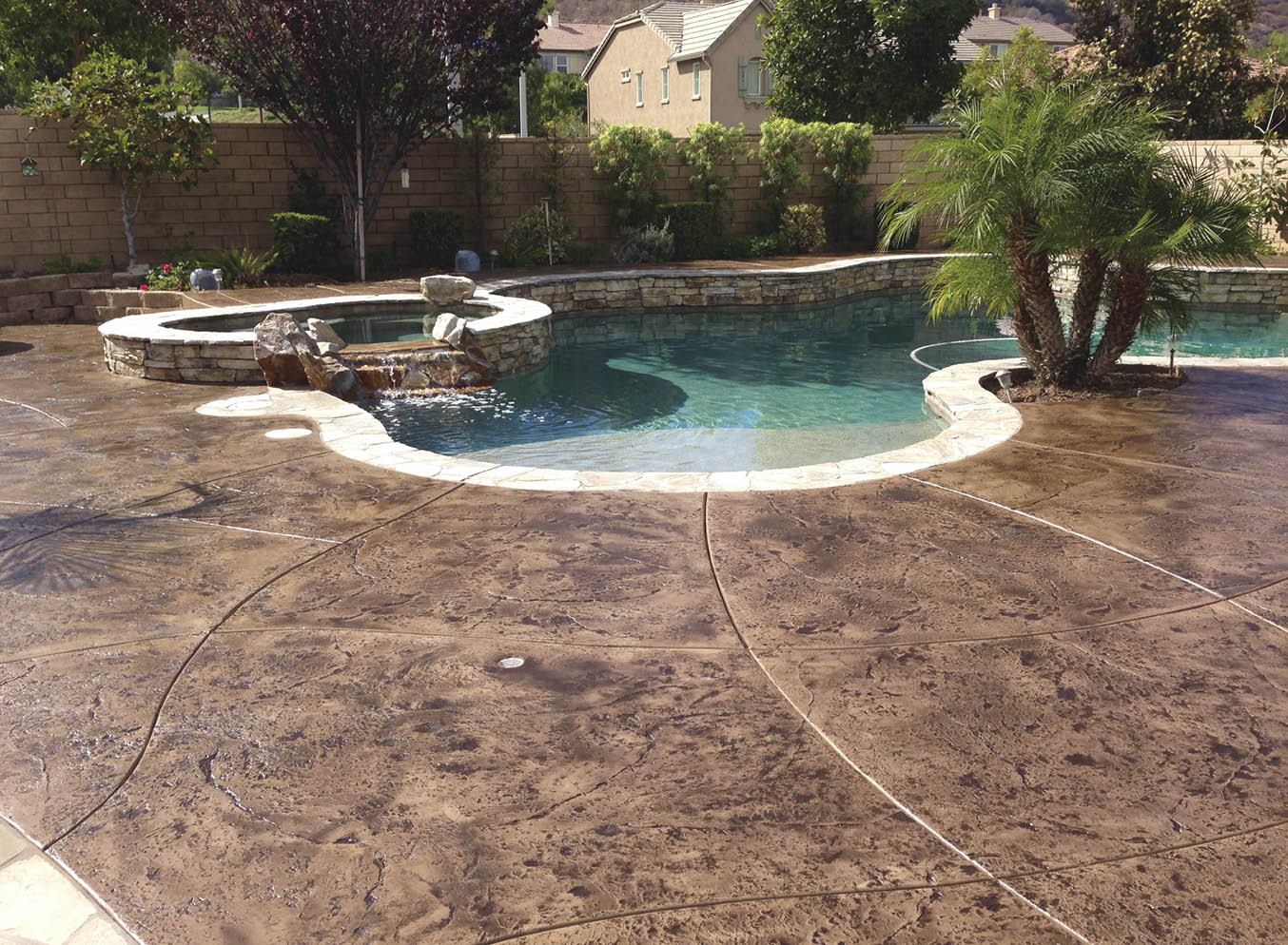 Pool with stamped and stained concrete deck and a hot tub spilling water over a water fall.