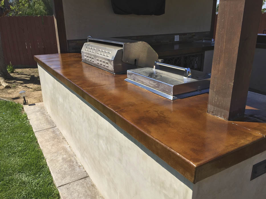 Deep brown concrete countertop in an outdoor kitchen setting.
