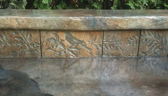 Concrete sitting wall carved with birds and branches and leaves.