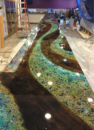 Floor in browns and teals with ribbons of colors flowing through.