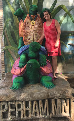 Cindee standing with her carved and painted turtle statues.
