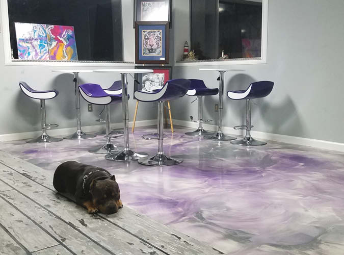 Pup lying on the floor next to a metallic epoxy