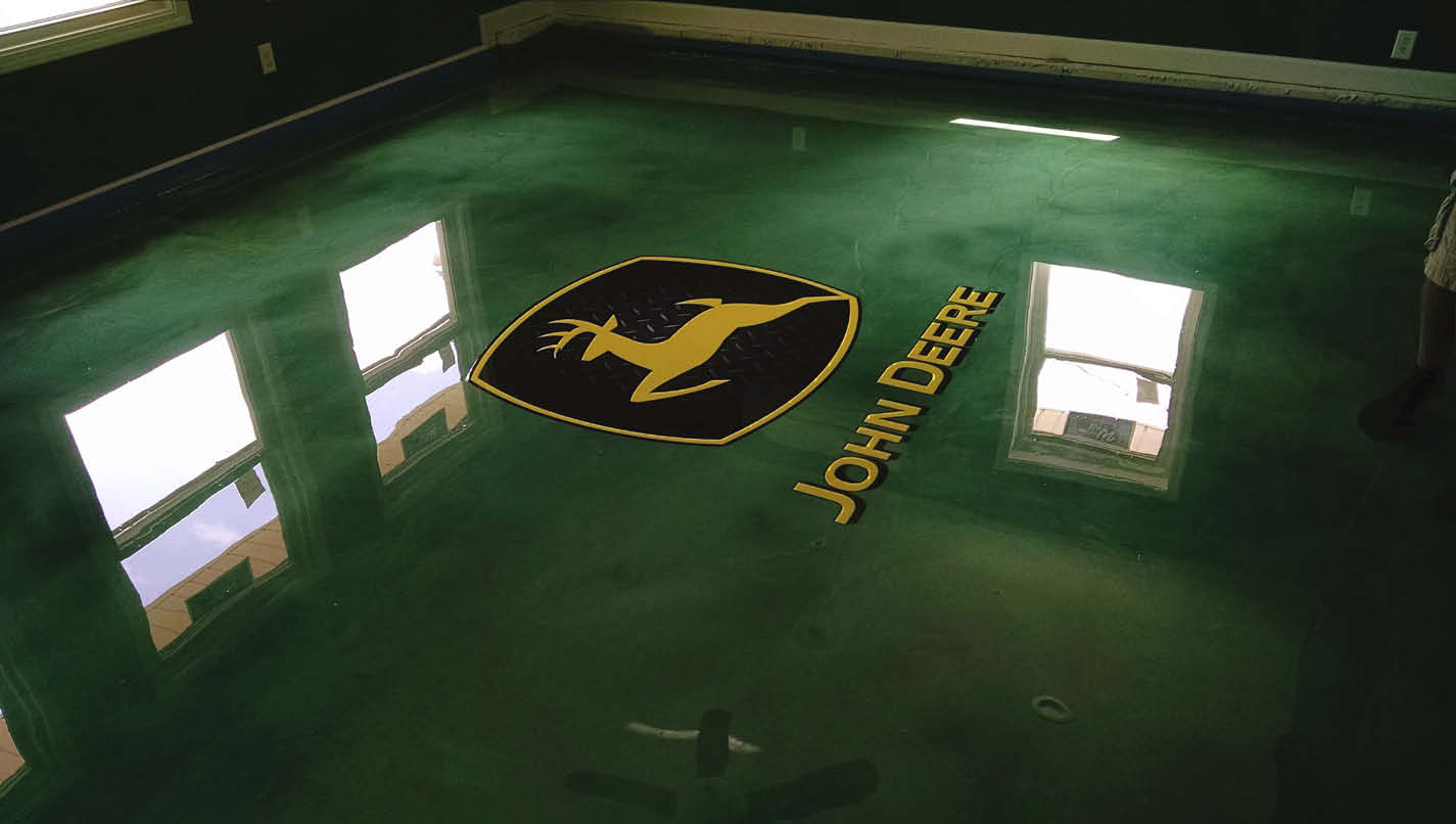 John Deere log on a green epoxy floor.
