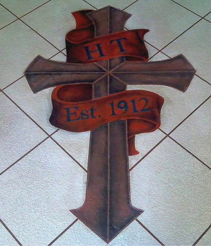 Cross stenciled and stained onto a checker pattern concrete floor.