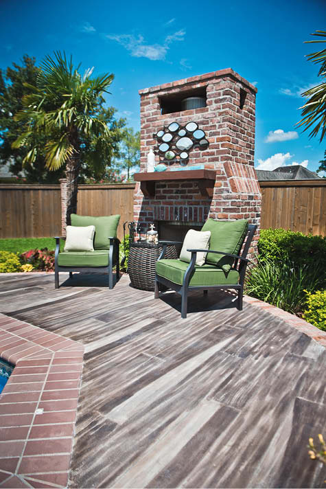 Outdoor fireplace with a pool deck of faux wood planks.