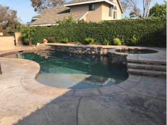 To bring new life to a faded and weathered pool deck and coping, two different earth-tone transparent stains were used in the field areas of the deck.