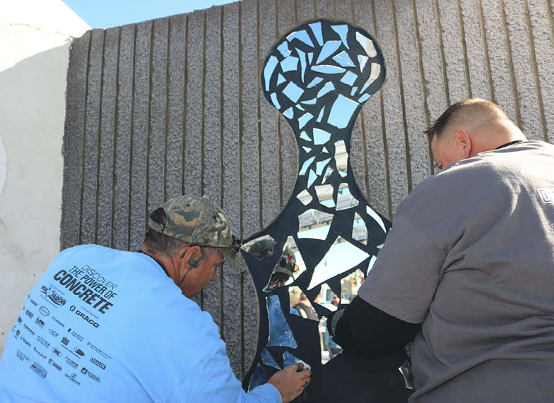 Matt Sampson and Mark Haen work on a glass insert on a wall of the display.