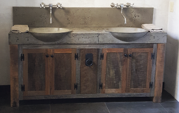 Two concrete sinks with chrome faucets on a wooden vanity.