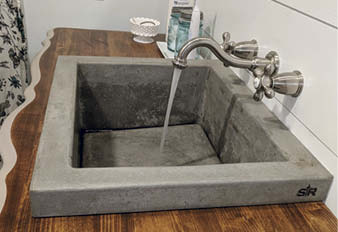 The 14-by-18-inch sink has a basin that slopes from 7 to 9 inches with a hidden drain and a slot that runs around the perimeter of the base.
