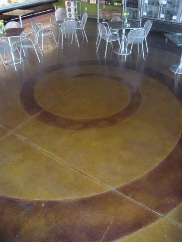 Swirl design on a concrete floor with reds and yellows.
