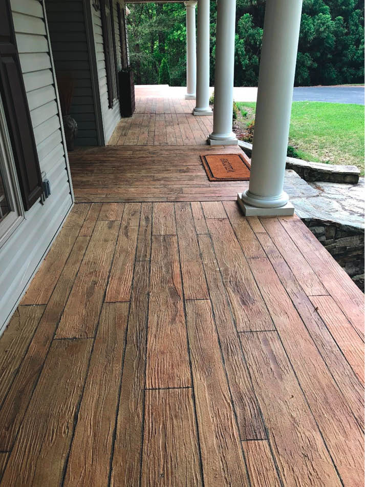This front porch had a concrete surface to begin with and was rejuvenated with an overlay colored and sculpted to look like wood planks.