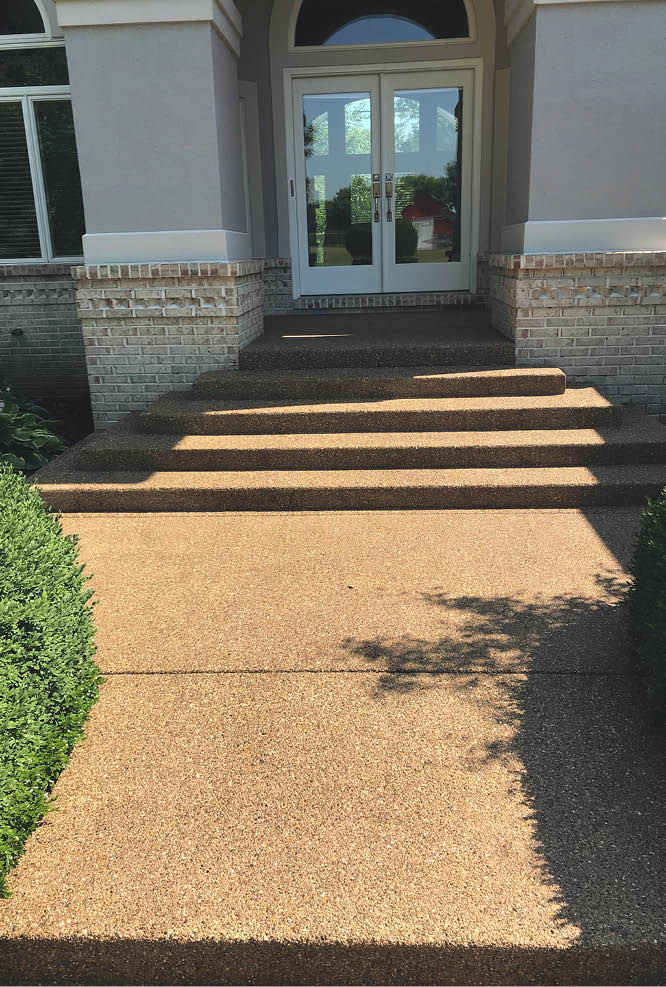 Concrete steps leading to a french door with exposed aggregate