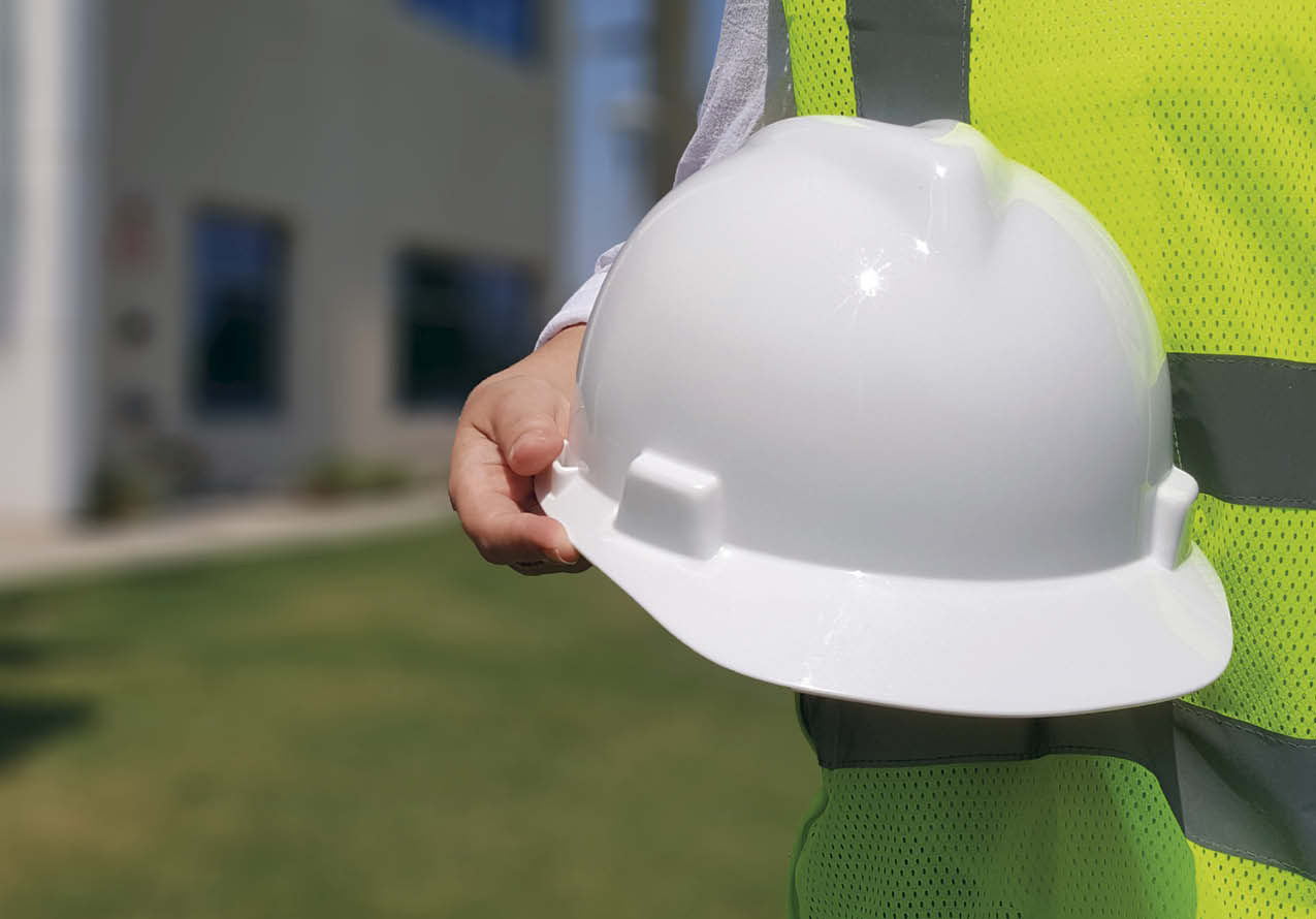 A person in a safety vest holding a white hard hat.